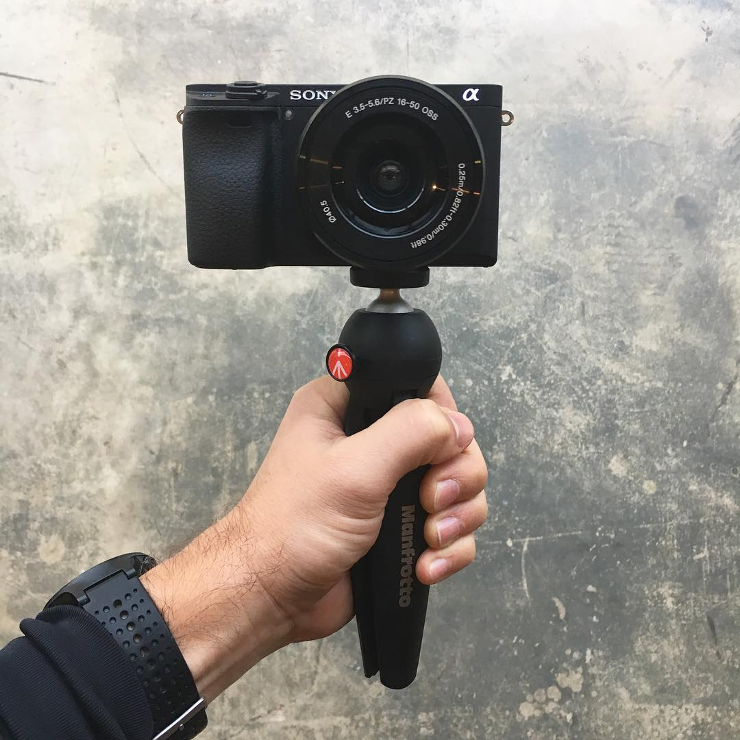 holding camera with small tripod